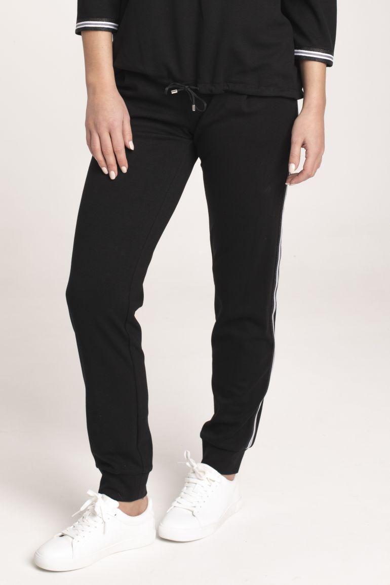 Modelka w czarnym dresie z lampasem Vito Vergelis. Czarna bluza ze stójką i taśmami i czarne spodnie Vito Vergelis.