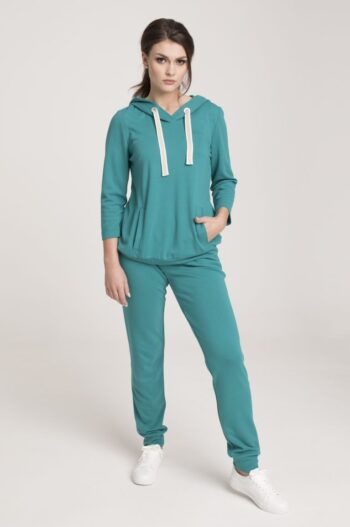 Modelka w zielonym dresie Vito Vergelis. zielona bluza z kapturem i kontrastowymi taśmami. Spodnie z lampasami.