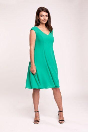 Modelka prezentuje sukienkę marki Vito Vergelis. Zielona sukienka z szyfonu z rozkloszowanym dołem i dekoltem V.